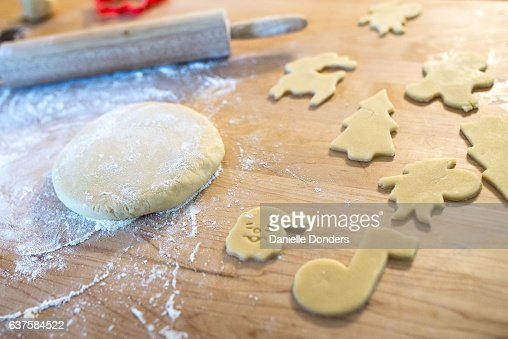 Rolled out sugar cookies being cut into Christmas shapes