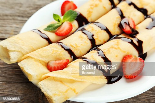 Rolled pancakes with strawberry on plate on grey wooden background : Stock Photo