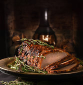 Creatively lit rolled pork roast with sage and thyme herb garnish shot against a rustic background with generous accommodation for copy space.