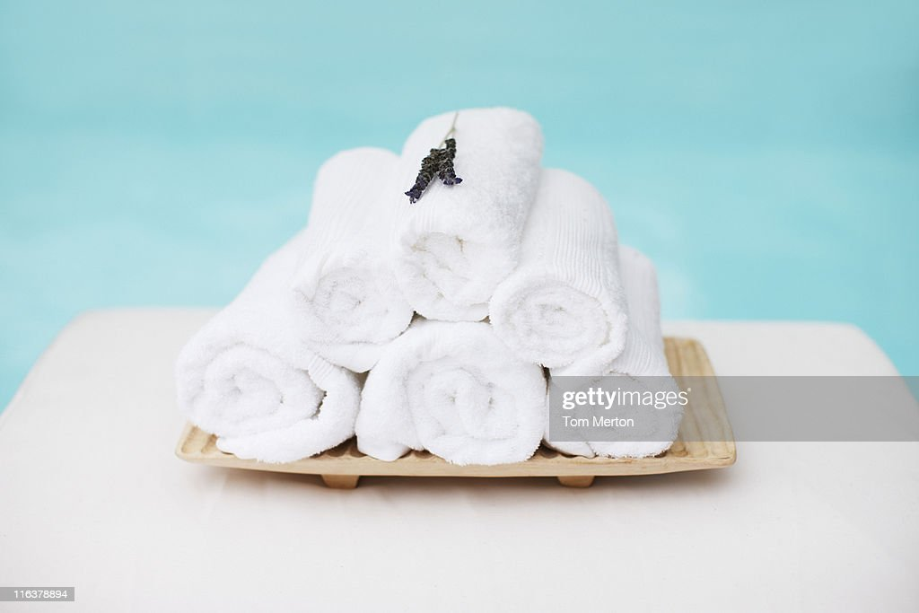 Rolled towels with lavender on tray at poolside