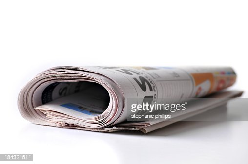 Rolled up Newspaper Lying on a White Background