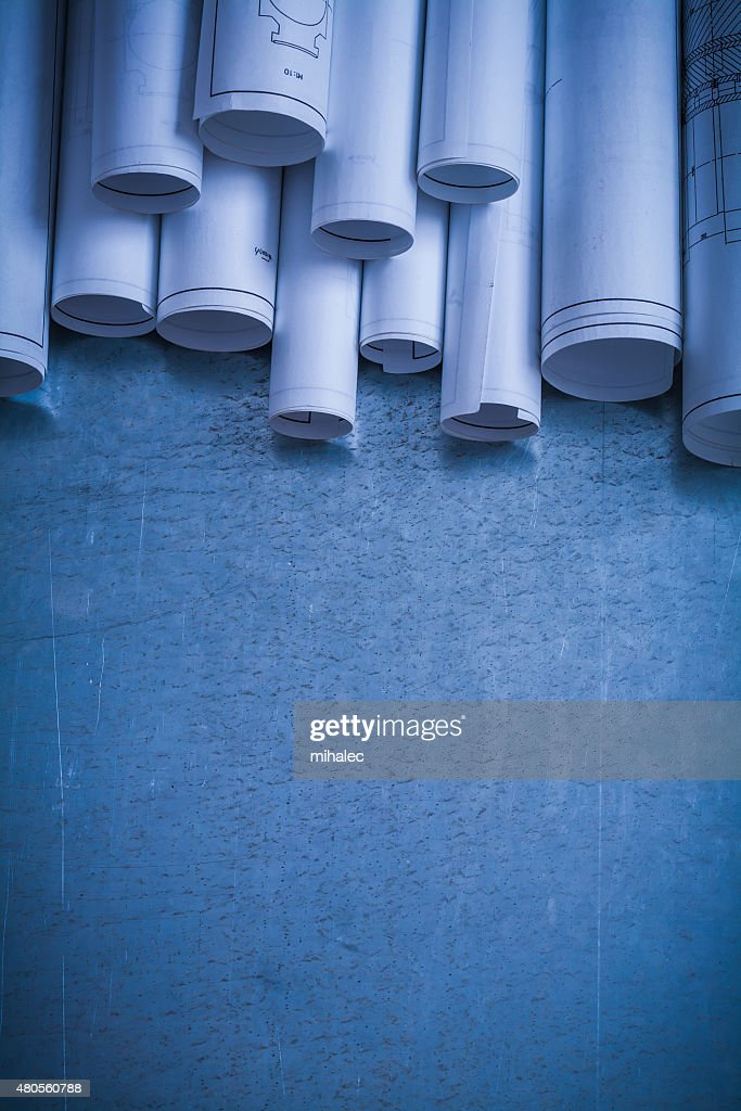 Rolled up white architectural blueprints on scratched metallic s : Stock Photo