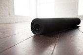 Rolled up yoga or pilates mat for exercise on natural wooden floor, sport class before or after practicing yoga, preparing for exercise, closeup