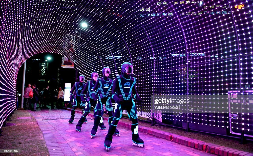 Rollerbladers glide through a light installation as landmarks around the city beaome part of Vivid Sydney, the annual festival of light, music and ideas, on May 23, 2013. More than 60 interactive and immersive light sculptures and installations across Circular Quay, The Rocks, Walsh Bay, Darling Harbour and North Sydney took part in the festival. City skyscrapers will light up along with 3D mapped projections on Customs House, Museum of Contemporary Art Australia, and Cadman's Cottage. AFP PHOTO / William WEST