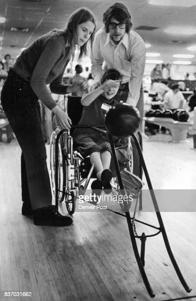 Rolling Along Despite Handicap Molly Mettler and Chuck Meschmeyer employes of United Cerebral Palsy of Denver help April Kane of 1575 Quebec St...
