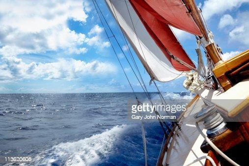 Rolling deck of yacht crashing through waves.