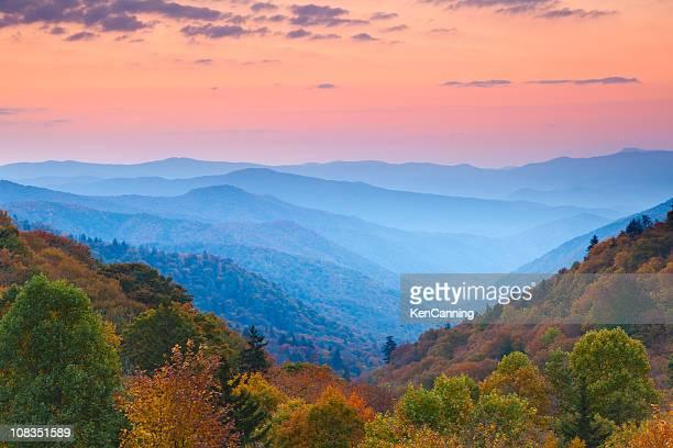 起伏のある山脈で日の出