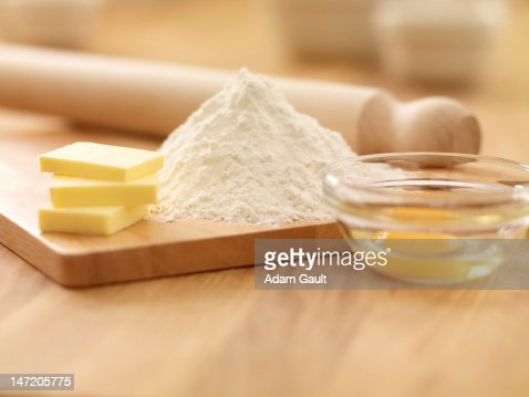 Rolling pin, flour, butter and egg on cutting board