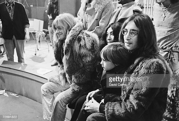 Rolling Stones guitarist Brian Jones artist Yoko Ono and her husband Beatles guitarist John Lennon with his son Julian on his lap at Internel Studios...