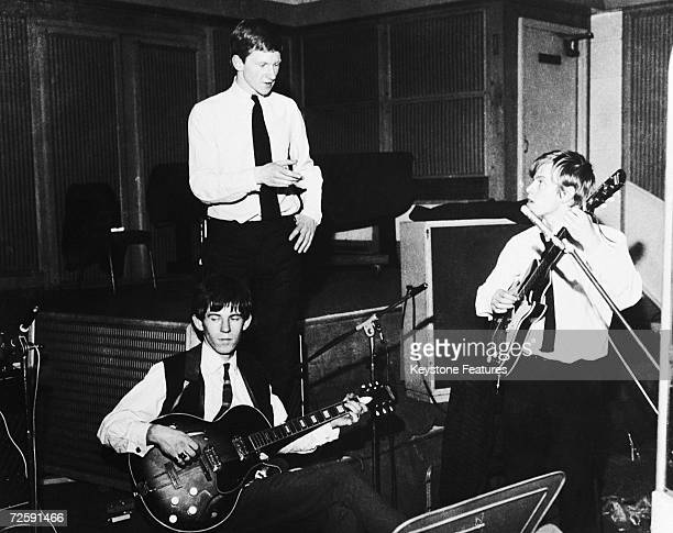 Rolling Stones manager Andrew Loog Oldham giving Brian Jones advice during an early Rolling Stones session while Keith Richards plays his guitar...