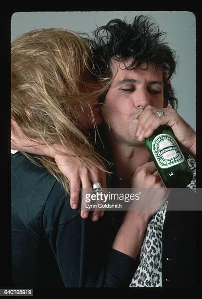 Rolling Stones rock star Keith Richards drinks a Heineken beer and hugs his spouse model Patti Hansen
