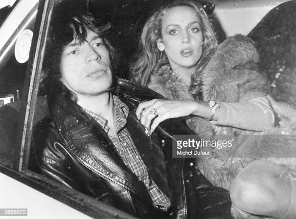 Rolling Stones singer Mick Jagger travels in the back seat of a car with his Texan fashion model girl friend Jerry Hall in Paris