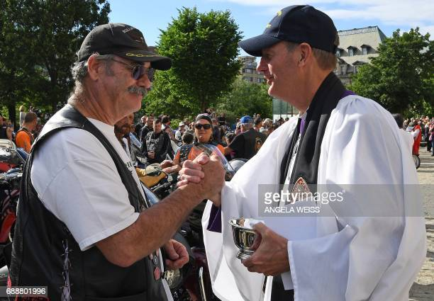 A Rolling Thunder member shakes hands after a reverend blessed his bike during the 'Blessing of the Bikes' at the Washington National Cathedral May...