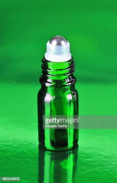 Roll-on bottle of Essential Oil on a green background