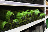 Rolls of artificial grass sale in the supermarket on the shelf