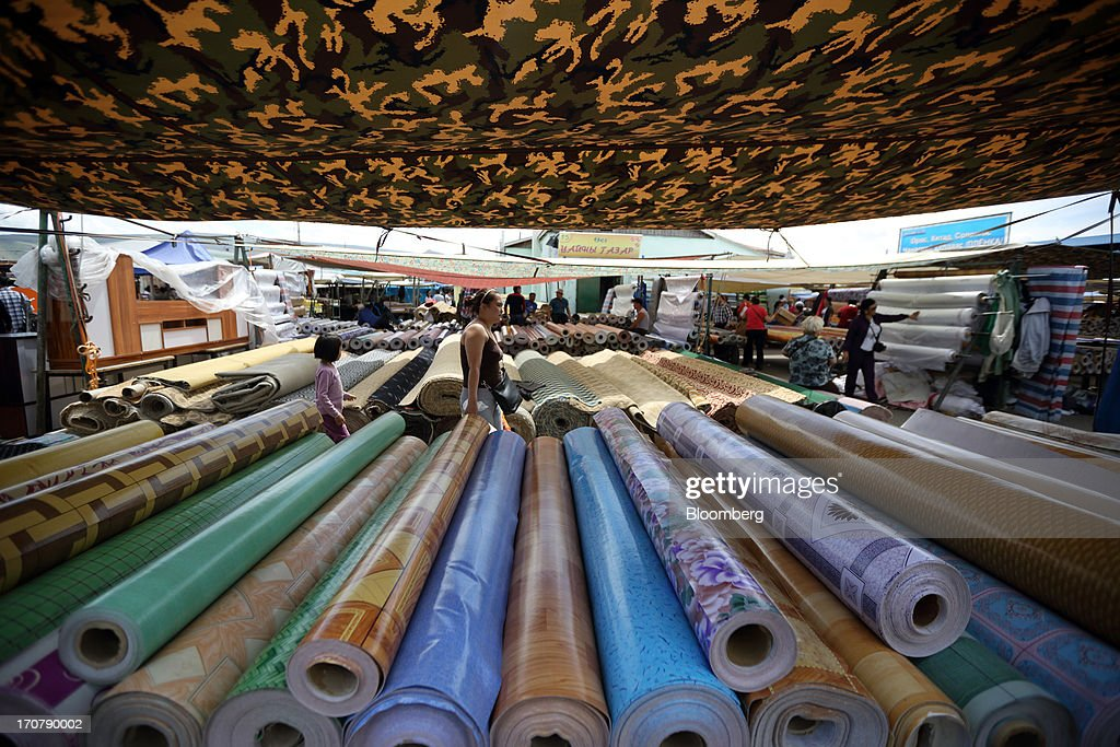 Rolls of carpets and linoleum are displayed for sale at a market in Ulaanbaatar, Mongolia, on Thursday, June 13, 2013. Mongolia, a country of almost 2.9 million people, is experiencing double-digit growth and new opportunities in the mining industry. Photographer: Tomohiro Ohsumi/Bloomberg via Getty Images