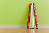 Rolls of Christmas wrapping paper leaning against wall