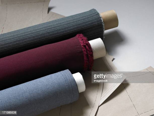 Rolls of fabric ion top of designs sheets