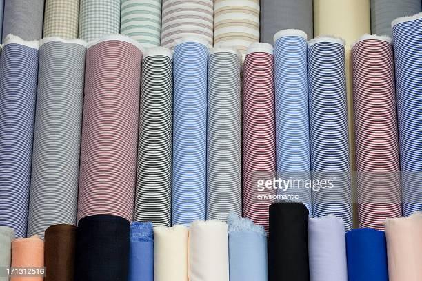 Rolls of multi-coloured cotton textiles.