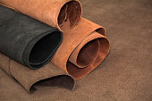 Rolls of natural brown and black leather. Materials for leather craft.