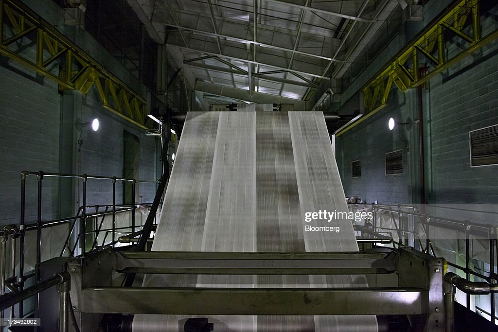 Rolls of printed paper come out of a press during the printing process of the O Globo newspaper in Rio de Janeiro, Brazil, on Thursday, July 11, 2013. Brazil economists raised their 2014 benchmark interest rate forecast to the highest all year, as policy makers work to slow inflation that has curbed consumption and confidence in the world's second-biggest emerging market. Photographer: Dado Galdieri/Bloomberg via Getty Images
