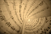 Close up of rolls of sheet music in sepia tone