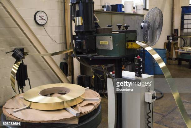 Rolls of thin brass are run through a stamping machine at the Zippo Manufacturing Co plant in Bradford Pennsylvania US on Tuesday March 21 2017 Zippo...
