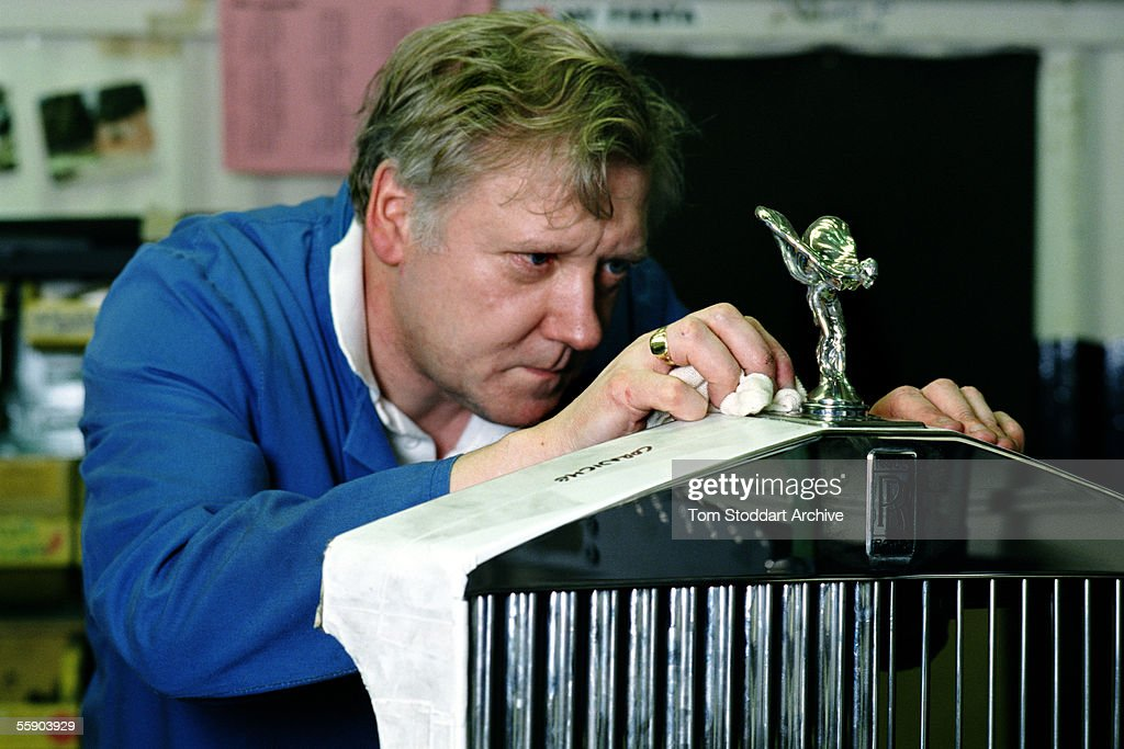 Rolls Royce assembly worker polishes the famous 'Flying Lady' on the grill of a Rolls Royce car