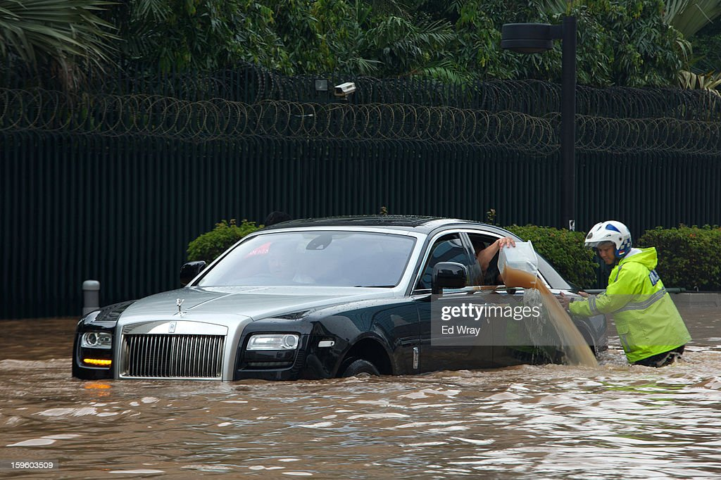 A Rolls Royce is stranded in floodwater in Jakarta's central business district on January 17, 2013 in Jakarta, Indonesia. Thousands of Indonesians were displaced and the capital was covered in many key areas in over a meter of water after days of heavy rain.