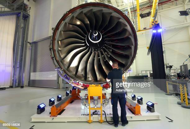 RollsRoyce Employee Oliver Nebelung assistant team leader in the company's Vertical Core Division inspects a RollsRoyce Trent XWB airplane engine to...