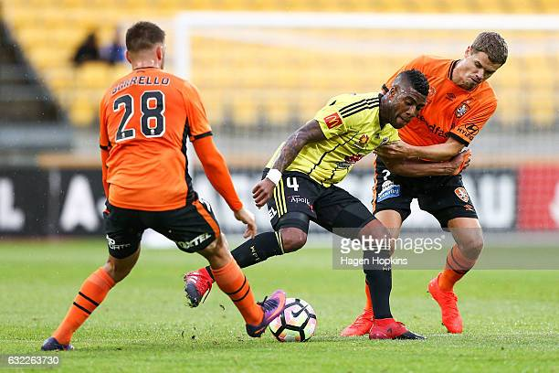 Roly Bonevacia of the Phoenix holds off the challenge of Thomas Kristensen and Brandon Borrello of the Roar during the round 16 ALeague match between...