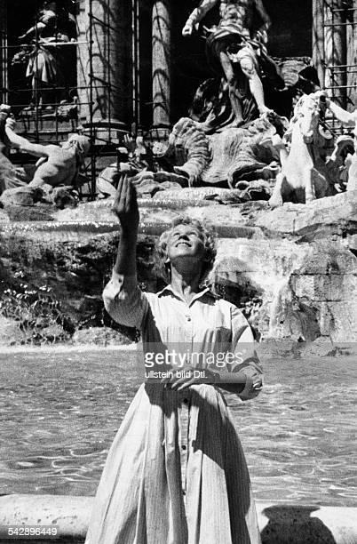 Rom Blonde Touristin steht mit dem Rücken zum TreviBrunnen und wirft eine Münze hinein 1956