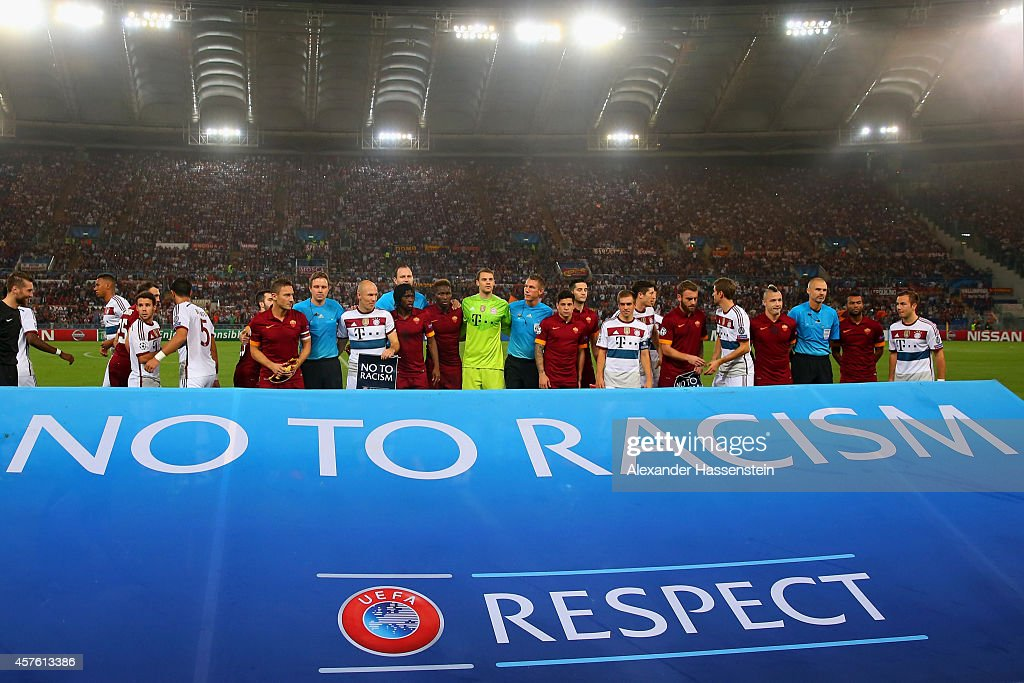 Roma and FC Bayern Muenchen pose behind a RESPECT banner displaying the message 'NO TO RACISM' before the UEFA Champions League group E match between...