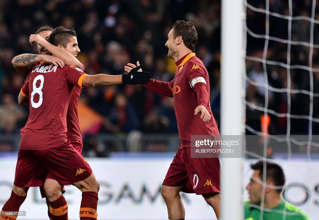 AS Roma Argentine forward Erik Lamela C celebrates after scoring with teammates AS Roma Argentine forward Pablo Daniel Osvaldo (rear) and AS Roma forward Francesco Totti R during the Italian Serie A football match between AS Roma and AC Milan on December 22, 2012, at the Olympic stadium in Rome.