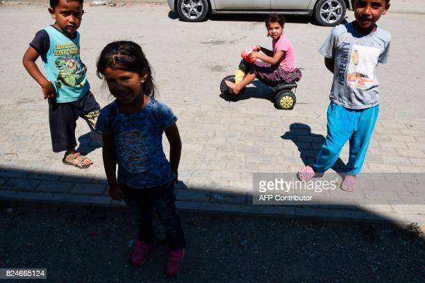 Roma children stand along a street in the Roma neighborhood in the town of Mitrovica on July 7 2017 The Roma 'are not treated like humans' Florim...