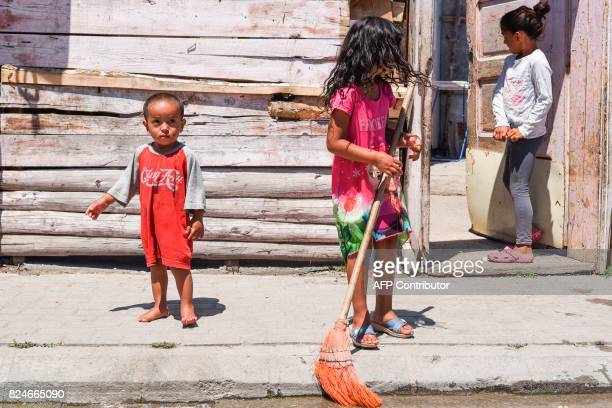 Roma children stand in front of their house in the Roma neighborhood in the town of Mitrovica on July 7 2017 The Roma 'are not treated like humans'...