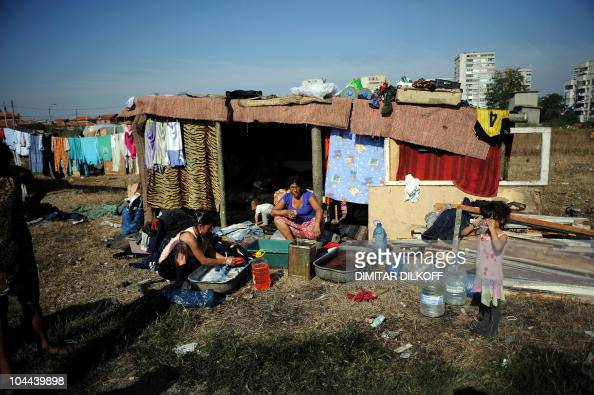 A Roma family wash clothes on September 17 in a makeshift camp built near the huge holedout shell of an apartment building and the pungent stench of...