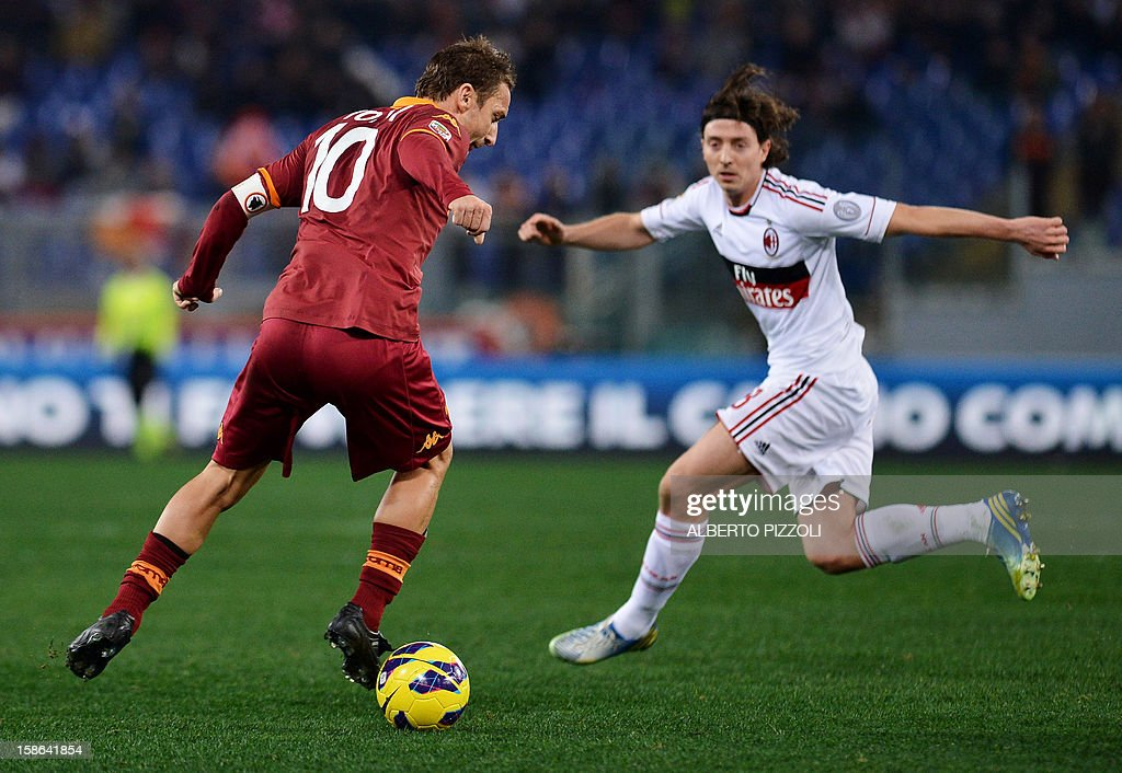 AS Roma forward Francesco Totti (L) vies for the ball with AC Milan's midfielder Riccardo Montolivo during the Italian Serie A football match between AS Roma and AC Milan on December 22, 2012, at the Olympic stadium in Rome.