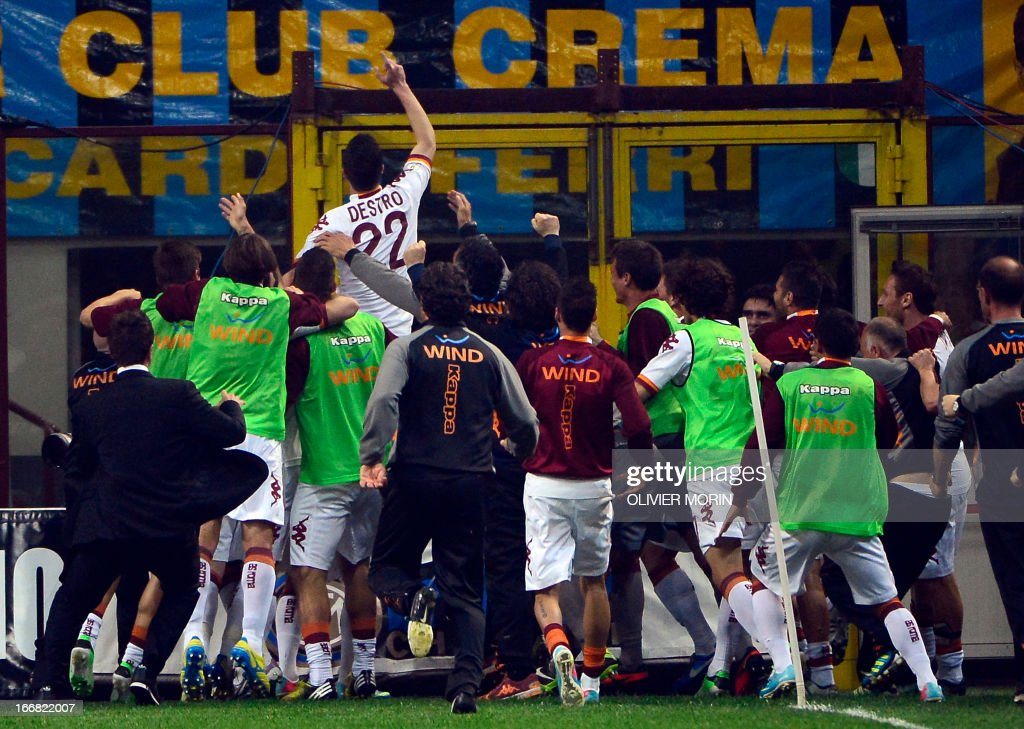 AS Roma forward Mattia Destro (Top) cheer supporters as he celebrates with teammates after scoring during the semi final second leg football match between Inter Milan and AS Roma, on April 17, 2013 in Milan, at the San Siro stadium .