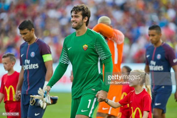 Roma goalkeeper Alisson left is lead on the pitch with teammates by youth escorts before an International Champions Cup match between AS Roma and...