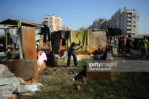 A Roma man builds a shack in a makeshift camp as the huge holedout shell of an apartment building and the pungent stench of tons of rubbish was all...