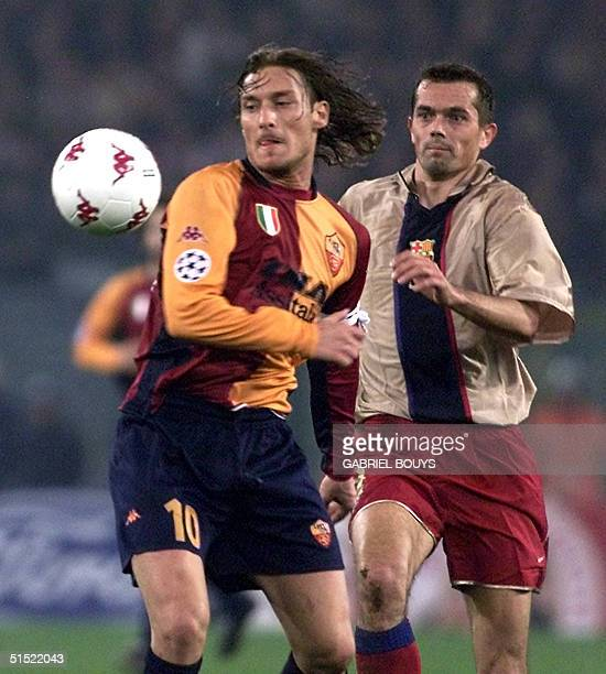 Roma midfielder Francesco Totti is chased by Barcelona's midfielder Dutch Philip Cocu during their Champions' League match AS Roma FC Barcelona at...
