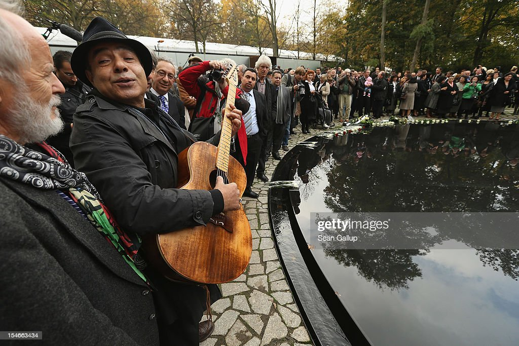 """Roma musician plays a guitar at the inauguration of the """"Memorial to the Sinti and Roma of Europe Murdered Under National Socialism"""" on October 24, 2012 in Berlin, Germany. In addition to targeting Jews during the Holocaust, Hitler also sought to exterminate the Roma population in Europe and estimates of the number killed range from 220,000 to 1,500,000."""