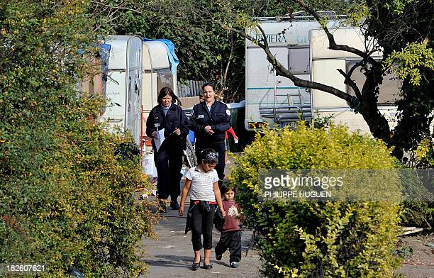 Roma people walk in front of French police as they carry out identity checks at a Roma camp on October 1 2013 in Roubaix northern France French...