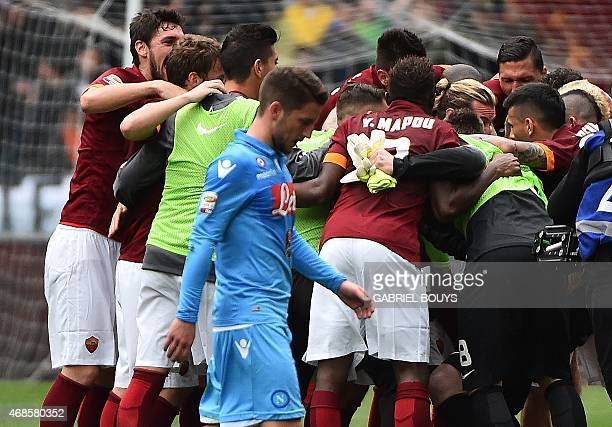 AS Roma players celebrate their victory as Napoli's forward from Belgium Dries Mertens looks dejected at the end of the Italian Serie A football...