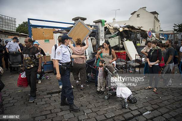 Roma stand outside their camp as police clear it before destroying it on July 21 2015 in Bobigny northeast of Paris Some fifty Roma people mostly...