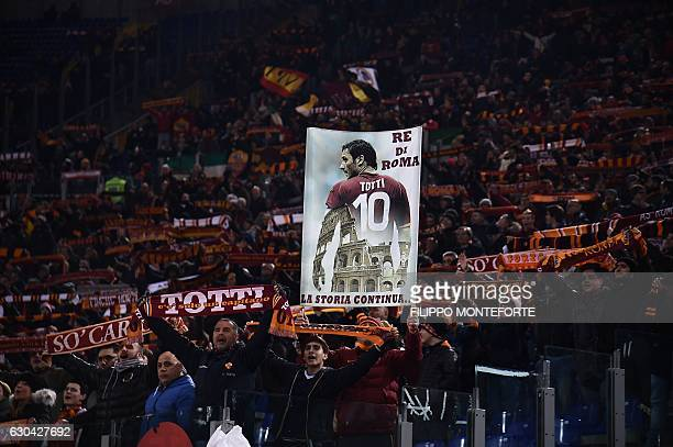 AS Roma supporters cheer holding a banner in honour of the team's captain Francesco Totti and reading 'King of Rome history continues' during the...