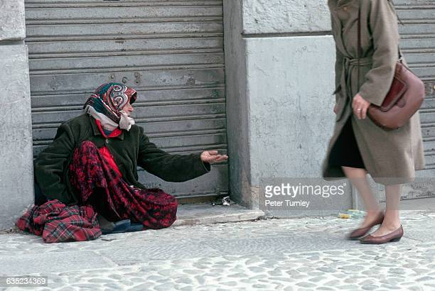 A Roma woman begs for change from a pedestrian on a sidewalk The Roma or Gypsies are travelling people and are often mistrusted by the societies in...