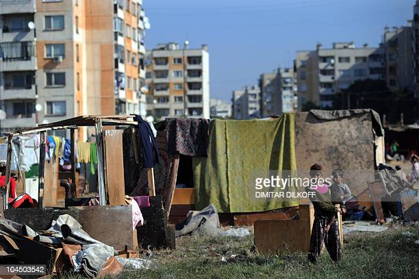 A Roma woman carries her child in a makeshift camp as the huge holedout shell of an apartment building and the pungent stench of tons of rubbish was...