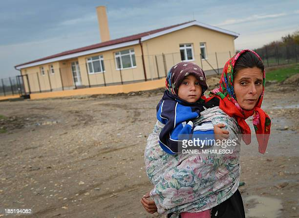 A Roma woman carrying her child walks in the front of the Roma centre in the Roma neighborhood in Tinca village on October 17 2013 A centre for Roma...